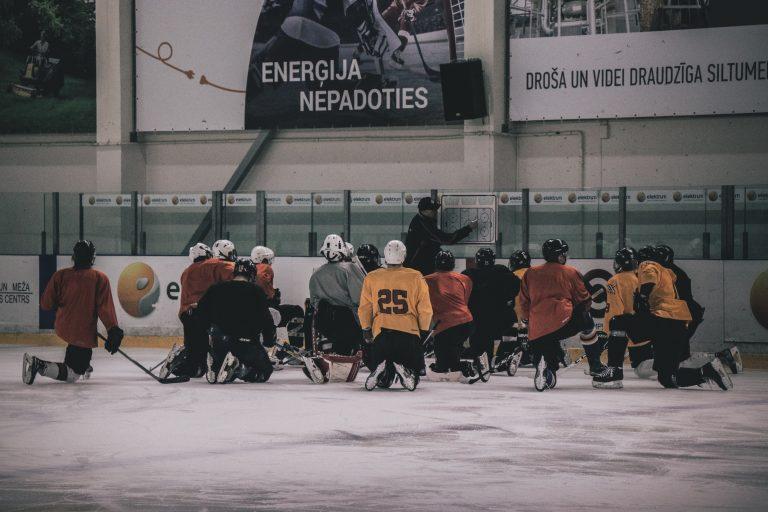 Eishockeytrainer gibt Anweisungen auf einer Taktiktafel am Spielfeld, die Mannschaft kniet im Halbkreis auf der Eisfläche
