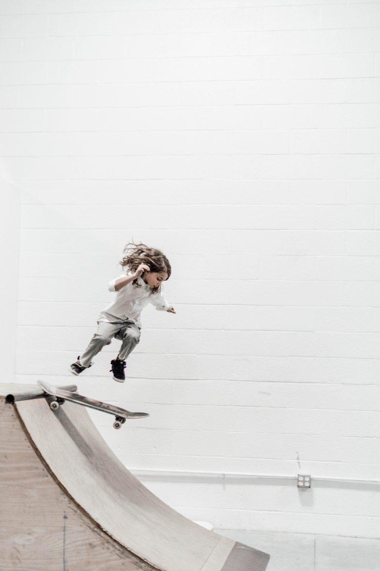 Kind mit Skatboard beim Sprung in eine Rampe