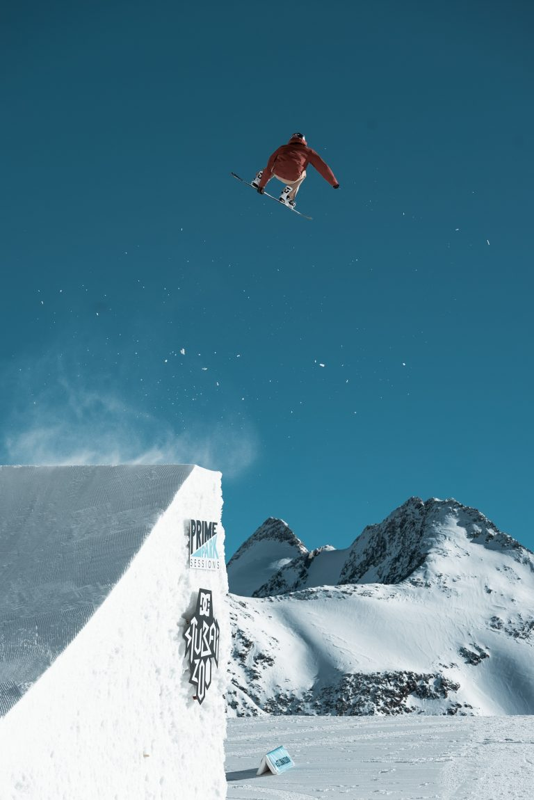 Snowboarder beim Sprung von einer Rampe an einem sonnigen Tag in den Bergen