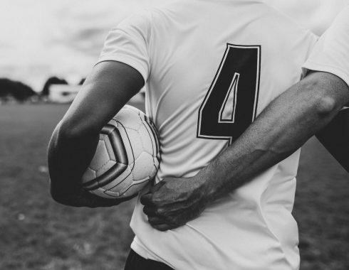 schwarzweißes Foto von Fußballer Rückenansicht, der den Ball in der linken Hand trägt und sich rechts mit be einem Teamkollegen einhängt