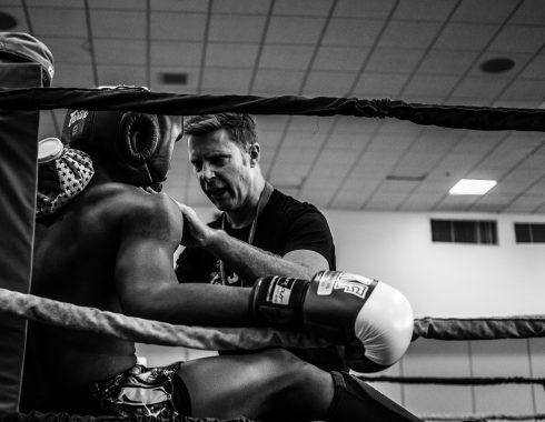 Boxer sitzt in der Ecke und wird von seinem Trainer instruiert